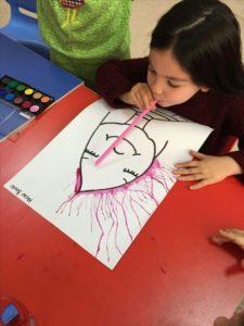 Dítě má před sebou papír s hrudkami tekutých barev. Do hrudek fouká brčkem, barva se rozbíhá po papíru a tvoří krásné obrázky.